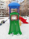 Colorful children's slide in the snow park area of ​​the city. On a winter day Royalty Free Stock Photography