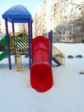 Colorful children's slide in the snow park area of ​​the city. On a winter day Stock Photos