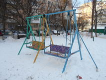 Colorful children's swings in the snow park area of the city Royalty Free Stock Photography