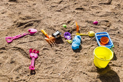 Colorful children's toys scattered on the sand at the beach Royalty Free Stock Image
