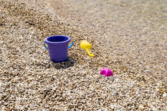Colorful children's toys scattered on the sand at the beach Royalty Free Stock Photography