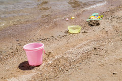 Colorful children's toys scattered on the sand at the beach Stock Photography