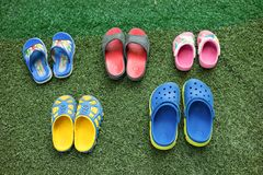 Colorful children sandals on playground made of artificial grass.  Royalty Free Stock Images