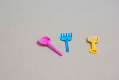 Colorful children toy, spoon fork on sand beach Royalty Free Stock Photography