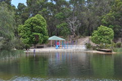Colorful childrens playground beside a lake in the country Stock Photos