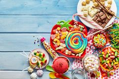 Colorful childs sweets and treats. Overhead view of colorful array of different childs sweets and treats in bowls on light blue wood background Royalty Free Stock Photo