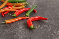 Colorful chili peppers on dark textured background. In contour light Stock Photography