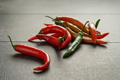Colorful chili peppers on dark textured background. In contour light Stock Image