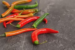Colorful chili peppers on dark textured background. In contour light Stock Photo