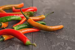 Colorful chili peppers on dark textured background. In contour light Royalty Free Stock Photos