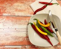 Colorful chili peppers on orange wooden background ... royalty free stock images