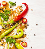 Colorful chili peppers and spices on white wooden Royalty Free Stock Images