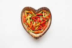 Colorful chili peppers in wooden dish heart shape. stock photography
