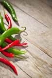 Colorful chili peppers on wooden table Royalty Free Stock Photos