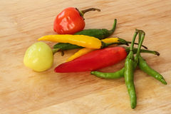 Colorful chili - red, green, yellow - wood background Royalty Free Stock Photos