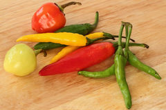 Colorful chili - red, green, yellow - wood background stock photo