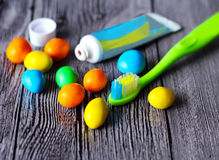 Colorful chocolate buttons and toothbrush Stock Photo