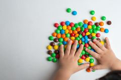 Colorful chocolate candies on white background with child hand. Multicolor chocolate candies on the white background stock photography