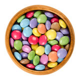 Colorful chocolate candies in wooden bowl over white Stock Photography