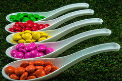Colorful chocolate candy. Served on spoons with green grass background Royalty Free Stock Photos
