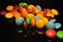 Colorful chocolate candy isolated on black background stock images