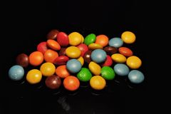 Colorful chocolate candy isolated on black background stock image