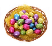 Colorful chocolate easter eggs in basket isolated Stock Photo