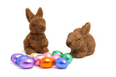 Colorful chocolate easter eggs and bunnies. Colorful chocolate easter eggs and brown bunnies over white background stock photo