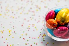 Colorful chocolate easter eggs in a transparent bowl with white background and blurred confetti royalty free stock photo