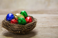 Colorful  chocolate eggs in a nest on a rustic wooden table, cop Royalty Free Stock Photos