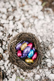 Colorful chocolate mini easter eggs in a birds nest on white stones Royalty Free Stock Photo