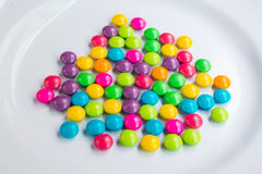 Colorful chocolate on white dish. Many colorful chocolate on white dish Royalty Free Stock Images