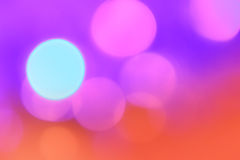 Colorful Christmas abstract background with bokeh lights. In violet, pink and orange Royalty Free Stock Image