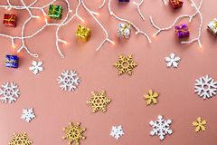 Colorful Christmas background with snowflakes, presents and Christmas lights on a warm brown background. Top view Royalty Free Stock Photography