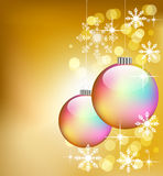 Colorful Christmas balls. Luminous winter illustration with two colorful Christmas balls on a sparkling background with white snowflakes Royalty Free Stock Photography