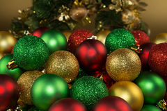 Colorful Christmas balls. With a Christmas crown in the background. Golden, red and green frosted and glittered balls stock photography
