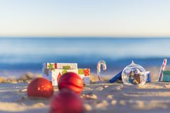 Christmas balls on the beach. Colorful christmas balls and gifts on the beach Stock Photo