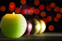 Colorful Christmas baubles with candle in the dark Royalty Free Stock Photos