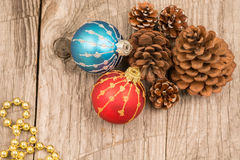 Colorful Christmas baubles, golden beads and pine cones top view. Red and blue Christmas baubles, golden beads and pine cones close-up Stock Image