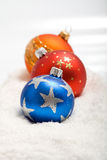 Colorful christmas baubles in the snow Royalty Free Stock Images
