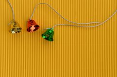 Colorful Christmas bells on yellow background Stock Images