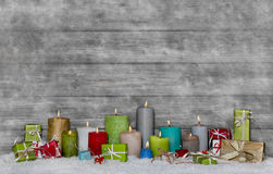 Colorful christmas decoration with different candles on grey and Royalty Free Stock Photos