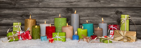 Colorful christmas decoration with presents and burning candles. Royalty Free Stock Images