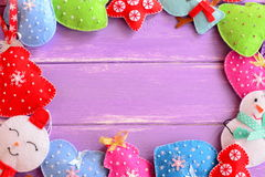 Colorful Christmas decorations. Cute felt Christmas trees, mittens, snowmen, hearts, stars on lilac wooden background Stock Photos