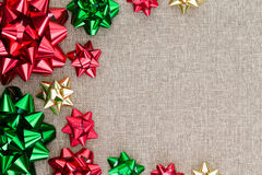 Colorful Christmas foil bow background on burlap. With a neat symmetrical arrangement in different sizes as a side border on the textured hessian textile with Royalty Free Stock Images