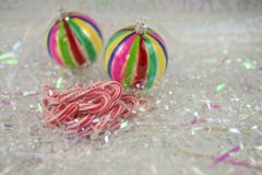 Colorful Christmas food photography picture with old fashioned candy cane sweets and bauble tree decorations in the background Royalty Free Stock Photography