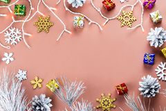 Colorful Christmas frame with snowflakes, presents and Christmas lights on a warm brown background. Top view Royalty Free Stock Image