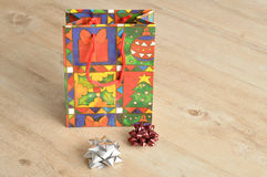 A colorful christmas gift bag with bows. On a wooden background Royalty Free Stock Image