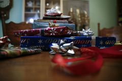 Colorful Christmas Gift Stack on Wooden Table. Stack of colorfully wrapped Christmas gifts on a wooden table, with ribbons and bows, and a blurry interior Stock Photography