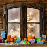 Colorful Christmas gifts on a windowsill. Colorful Christmas gifts and glowing multicolored candles on a windowsill of a rustic timber cabin with a view through Royalty Free Stock Photography